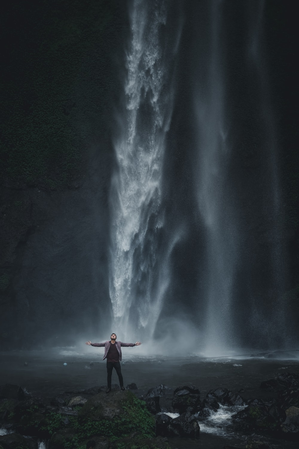 man in gray jacket standing near waterfalls
