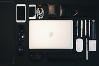 silver MacBook between Magic Mouse, pencil, sunglasses, and iPhone