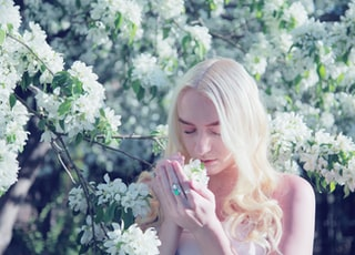 woman smelling flower during daytime