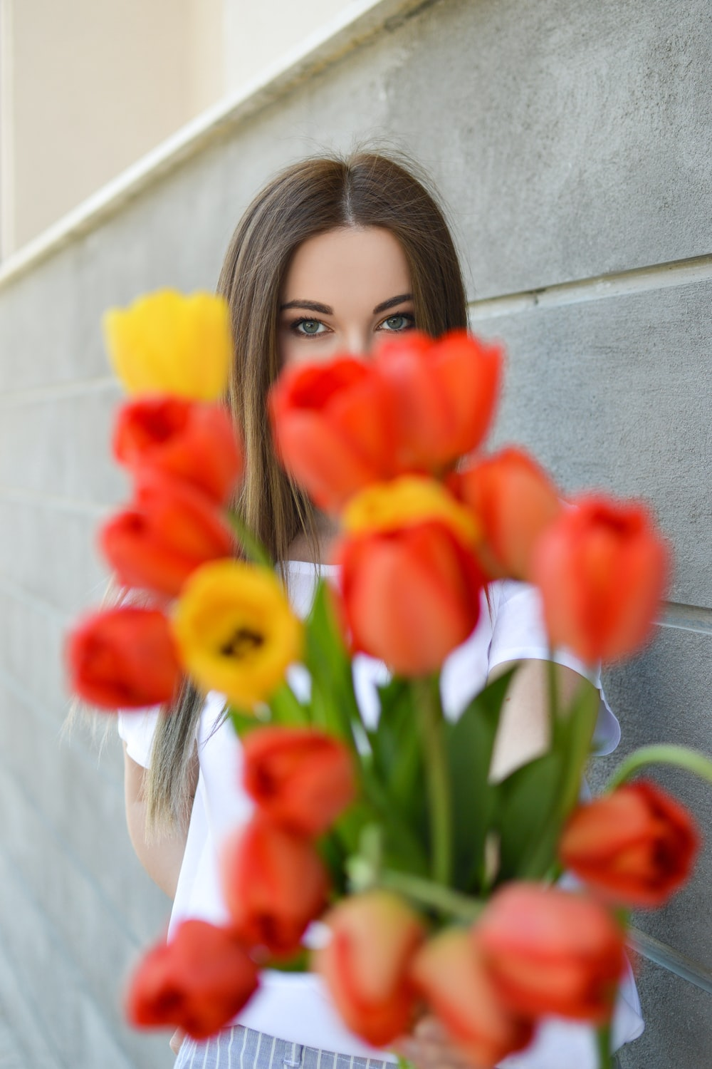woman holding orange and yellow flowers