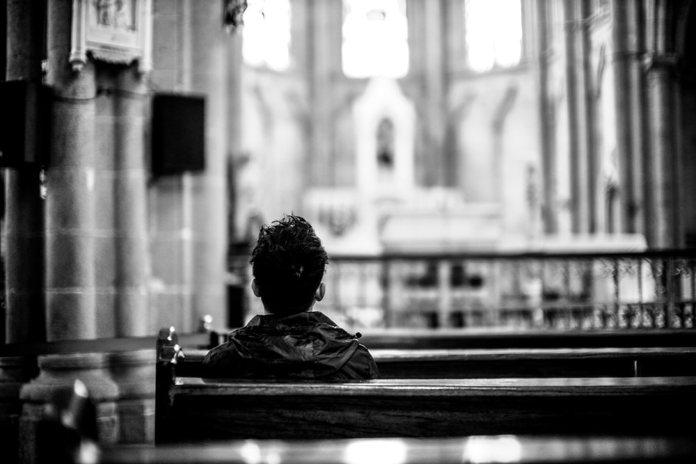 grayscale photo of man sitting on church pew inside church