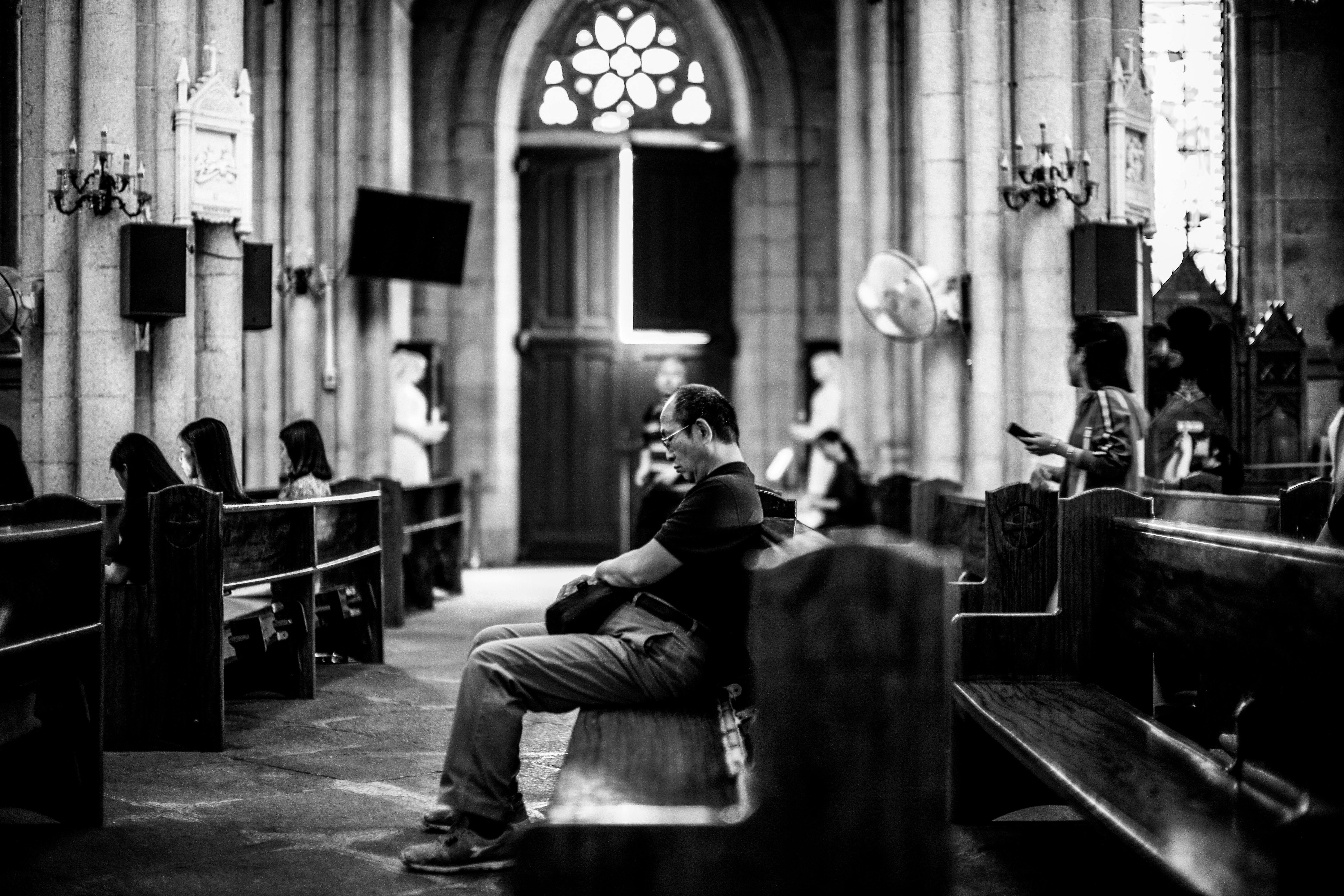 grayscale photography of man sitting on pew