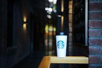 Starbucks coffee on top of wooden rail