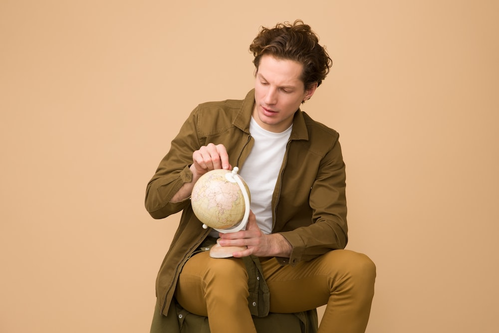 man holding globe while on sit