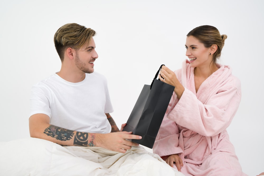 woman holding black paper bag sitting in front of the man