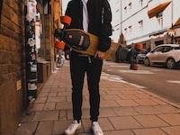 person holding skateboard near building