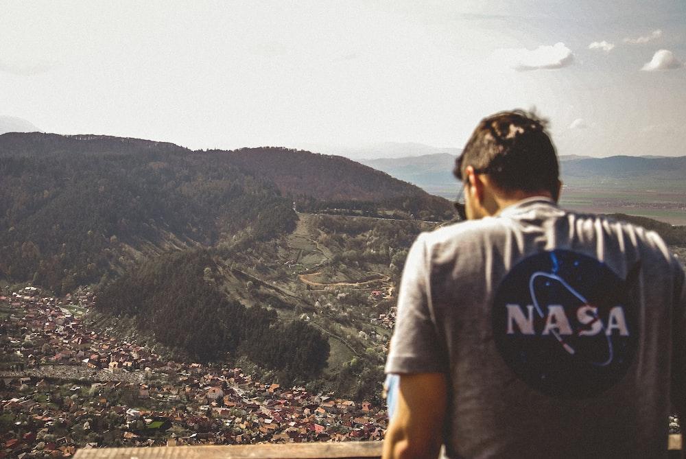 man facing city and mountain