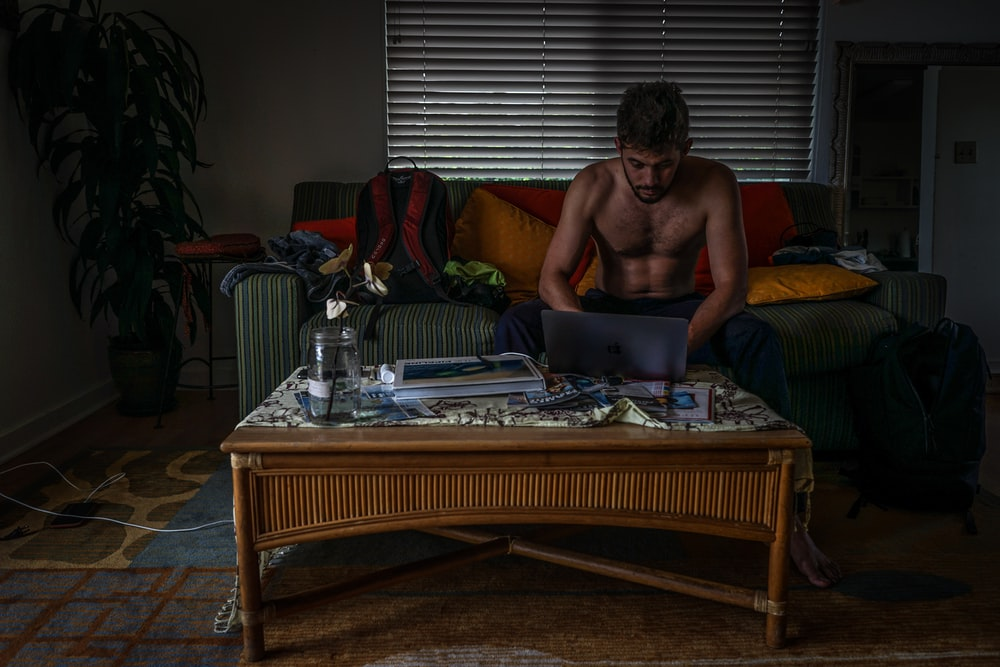 topless man front of laptop in living room set