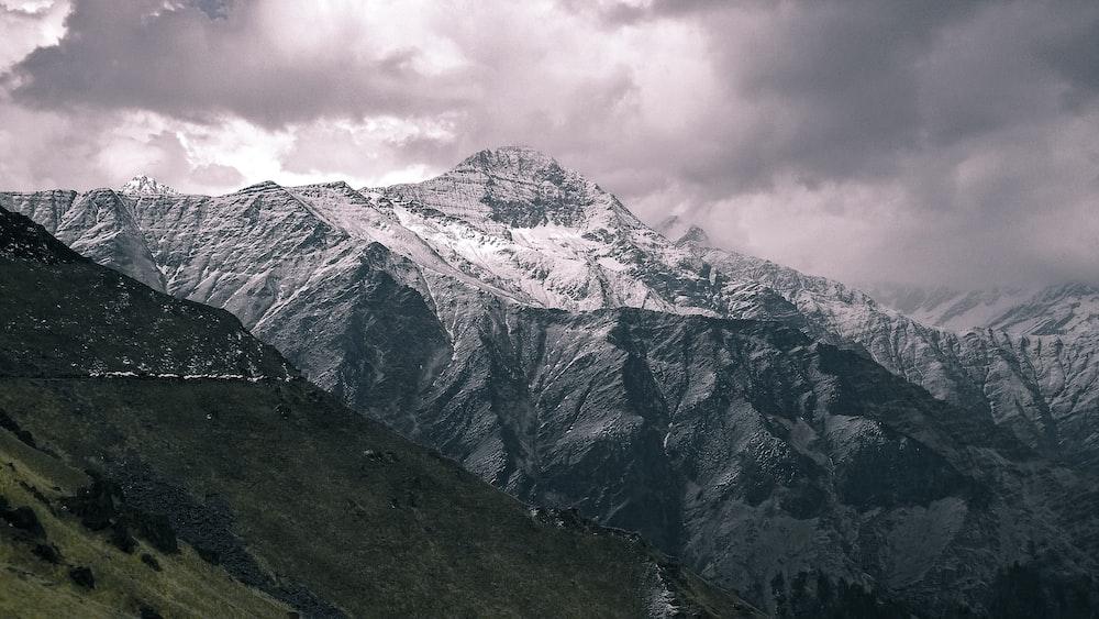 white snow cap mountain near green mountain under cloudy sky at daytime
