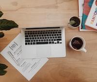 flat-lay photo of laptop near mug with liquid
