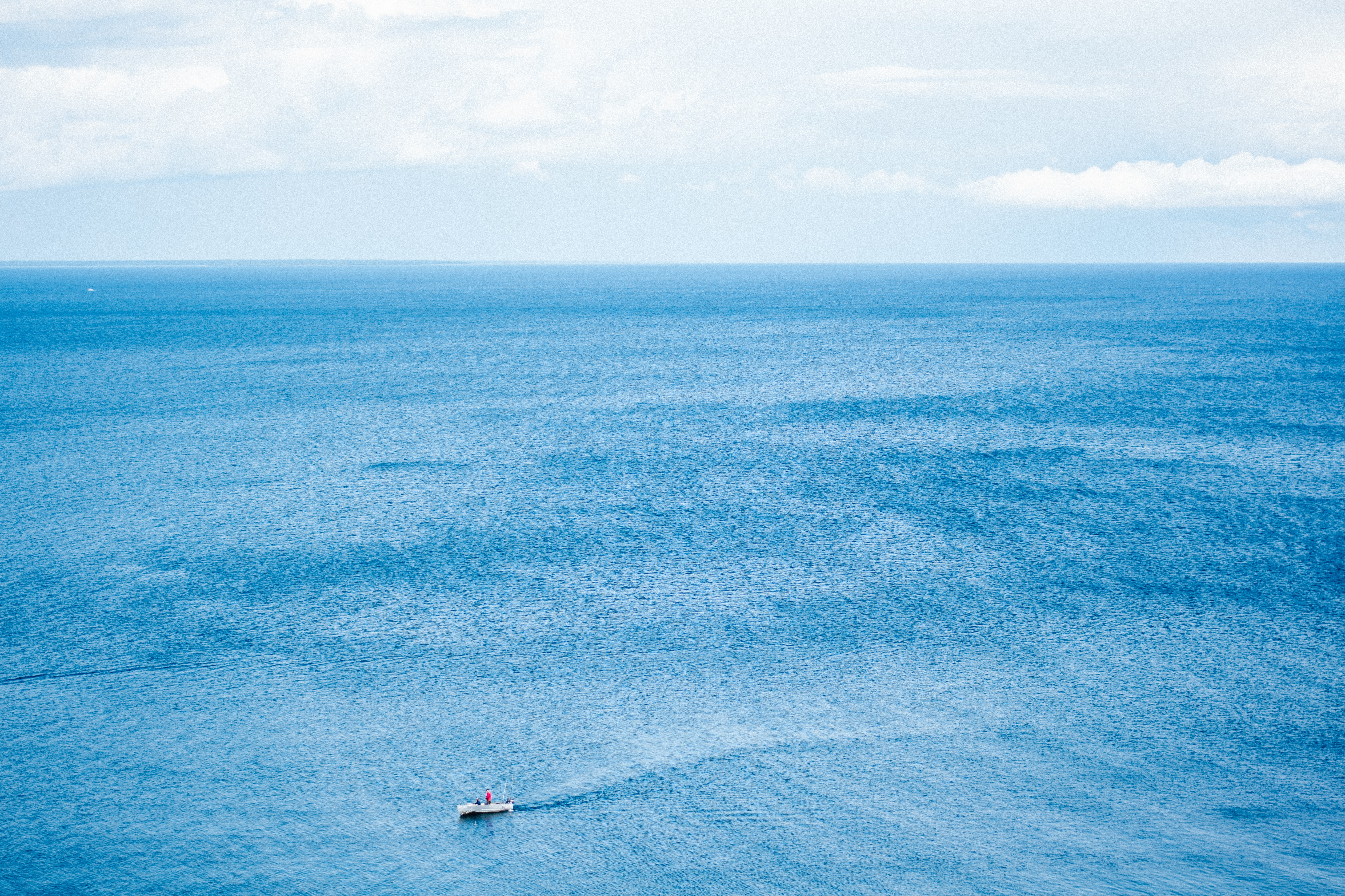 aerial photo of motor boat surrounded of body of water during daytime
