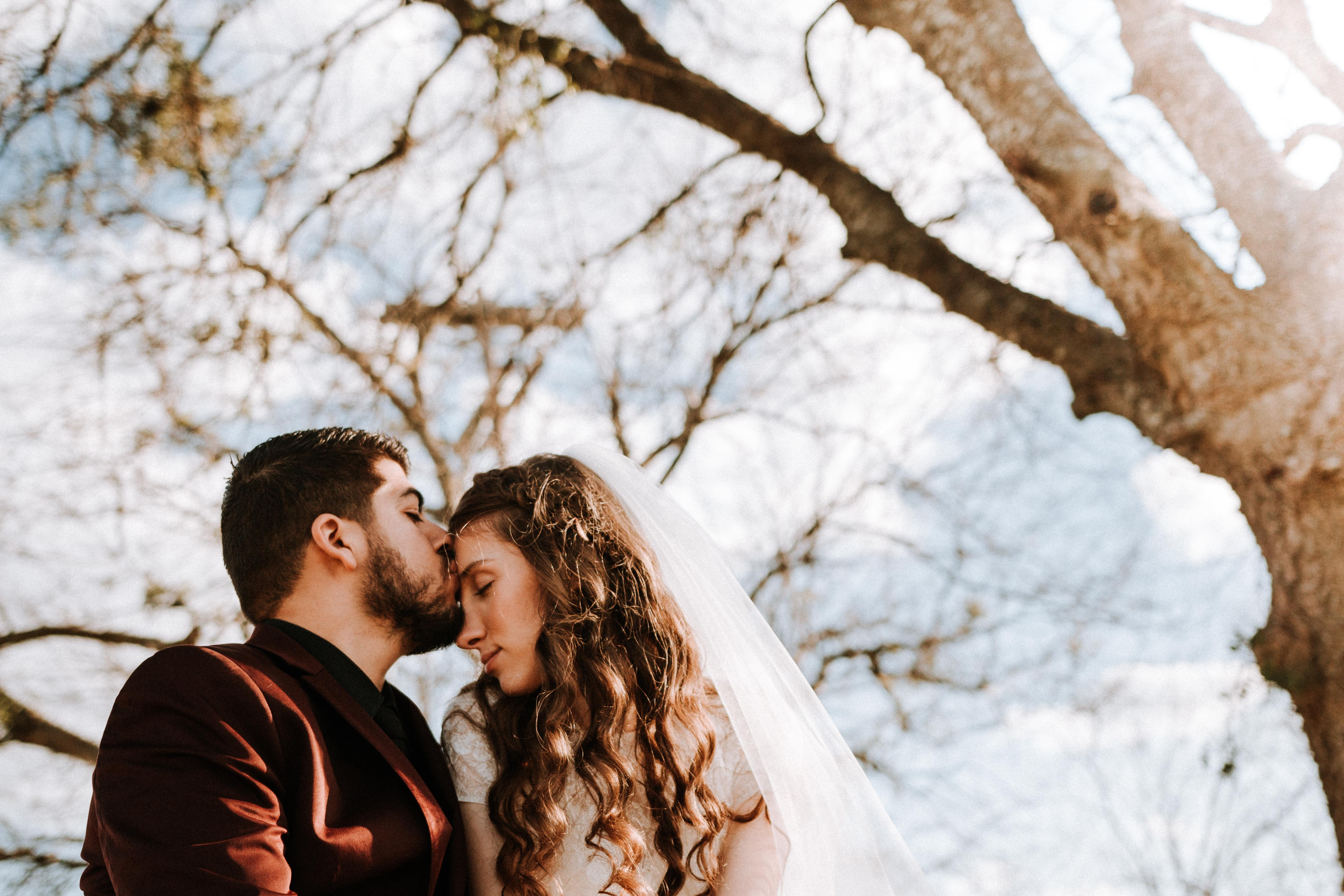 man kissing woman on forehead near bare tree during daytime