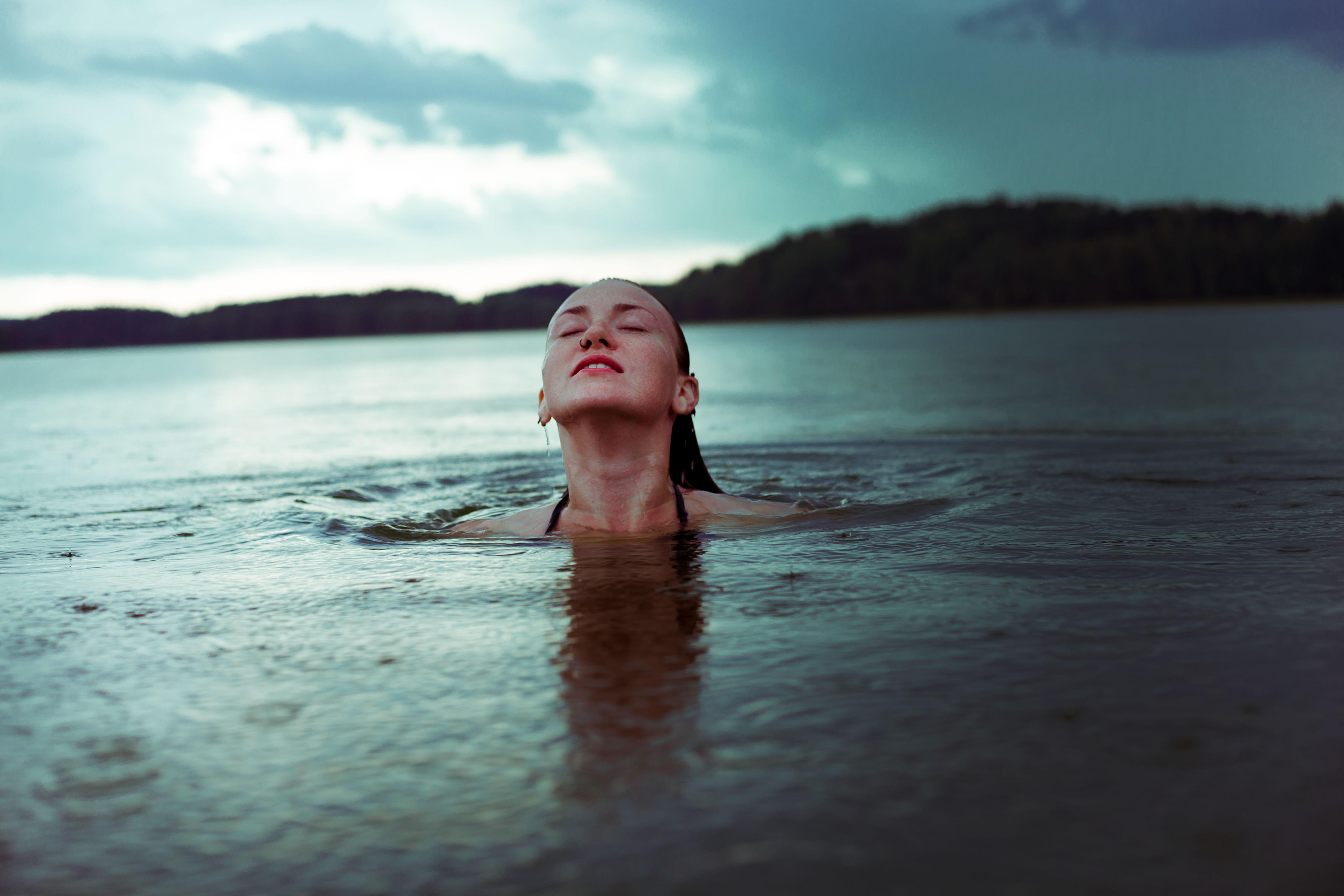 woman on body of water under cloudy sky during daytime