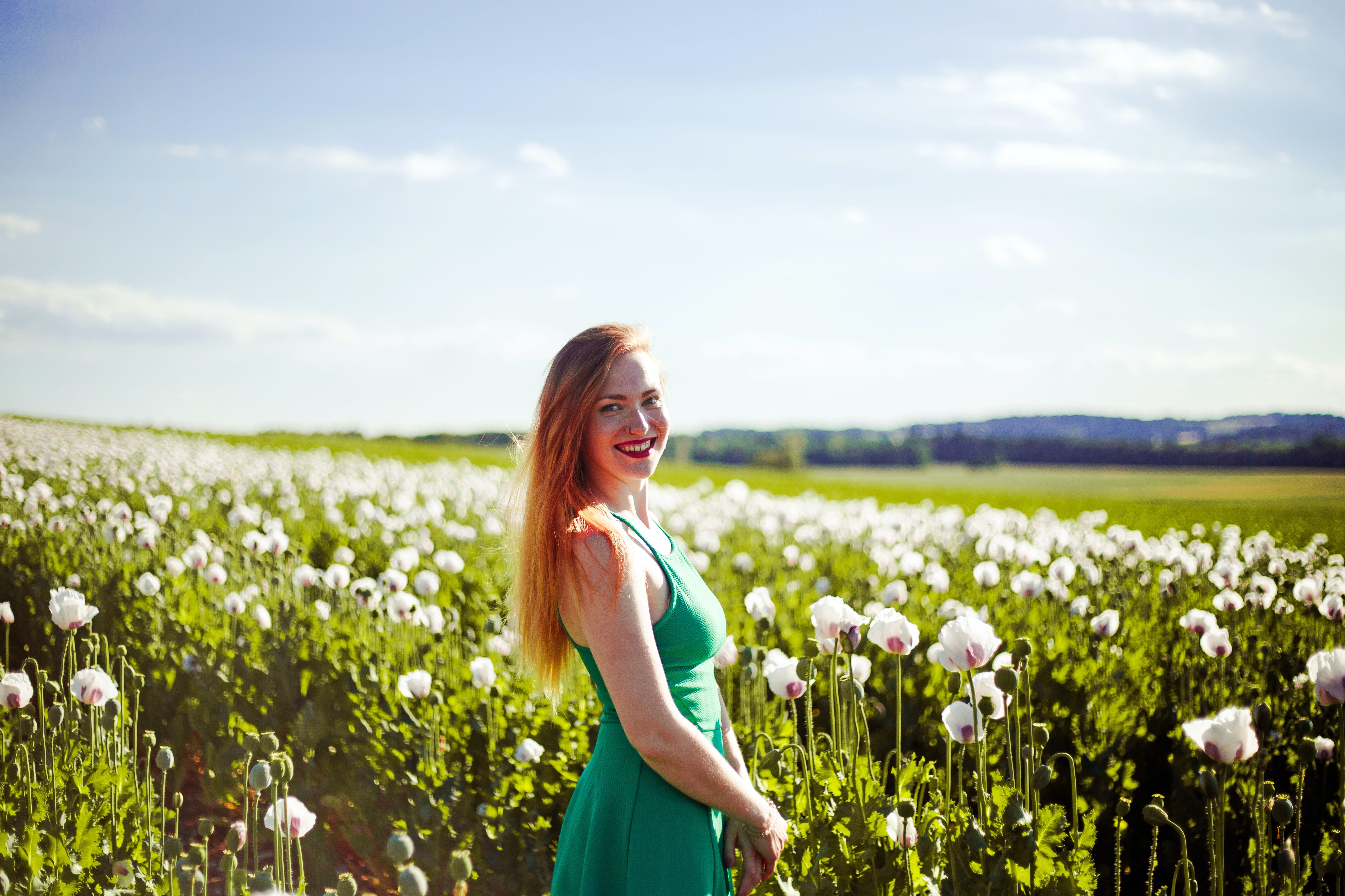 woman standing near white petaled flower field at daytime