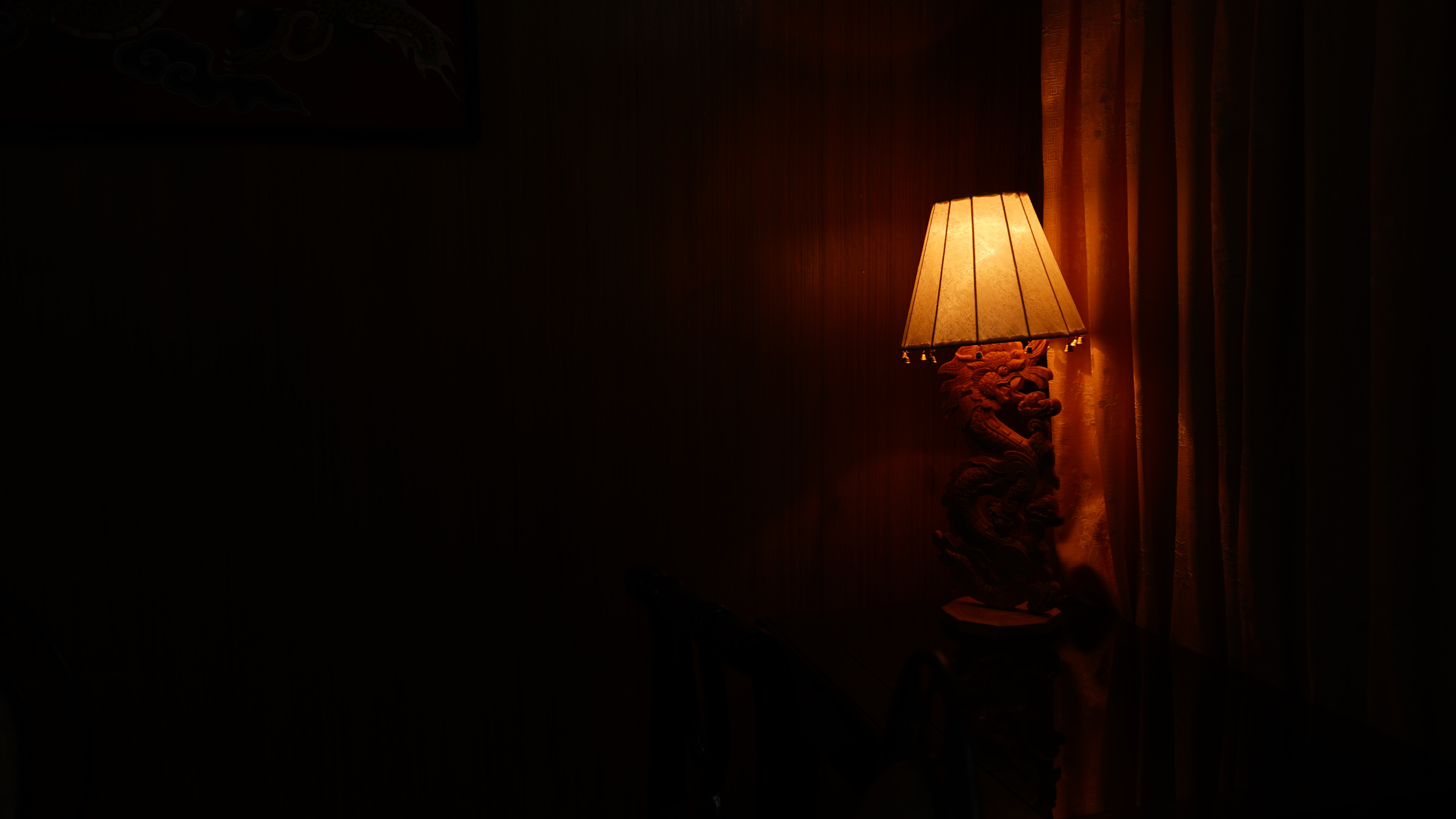photography of lighted table lamp near dim room