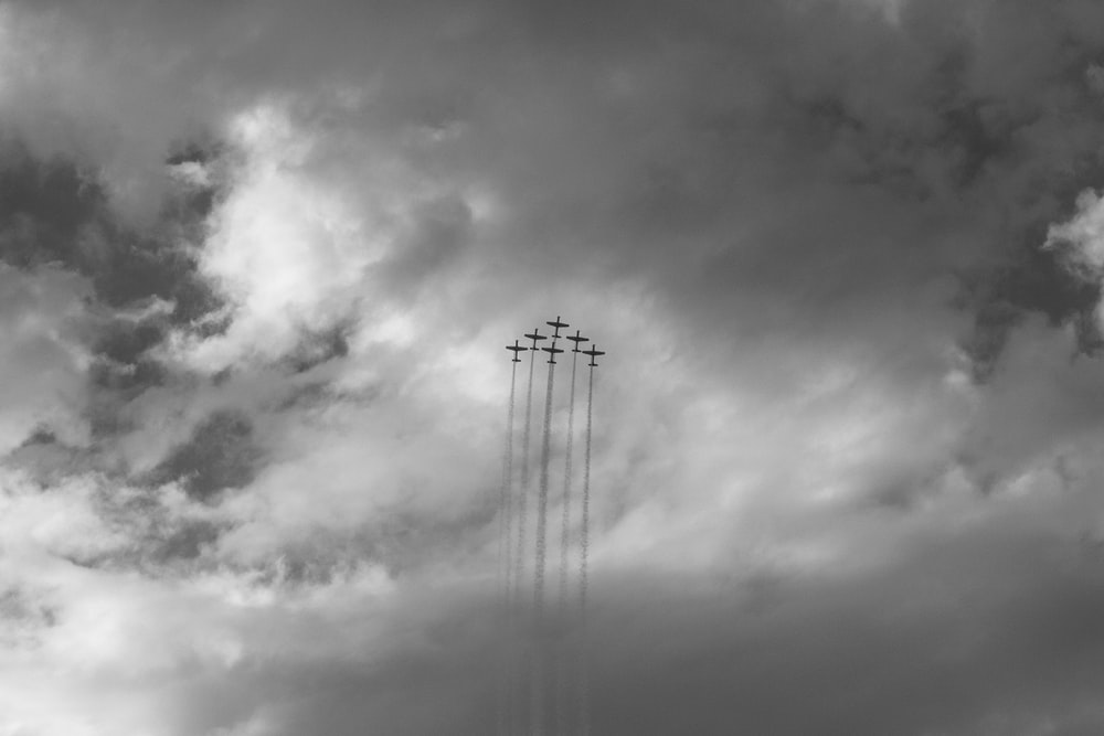 grayscale photo of six aircrafts creating contrails