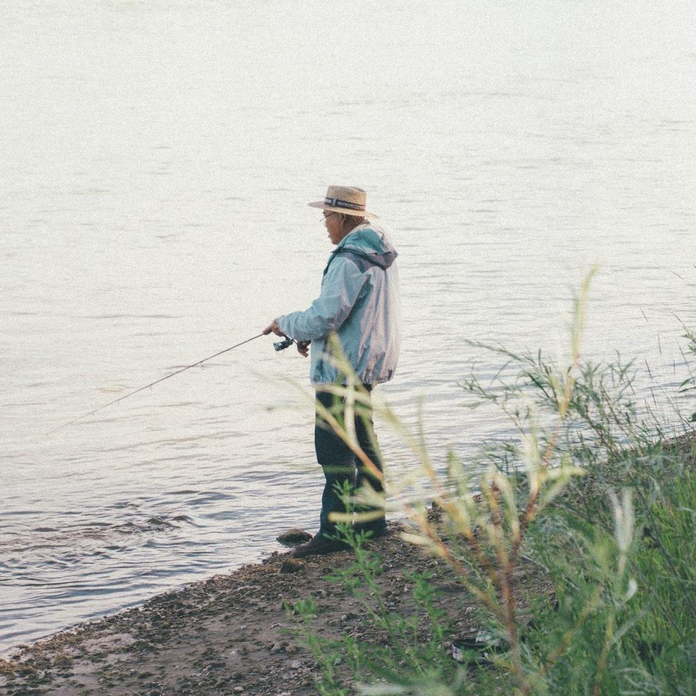 man fishing beside body of water during daytime photo