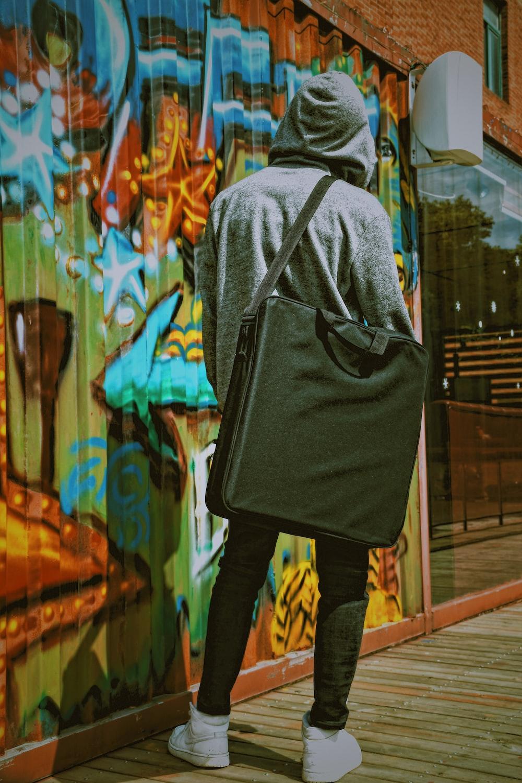 man wearing grey hoodie and black bag
