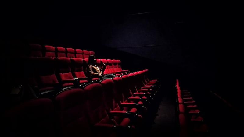 映画館で一人で映画をみる男性