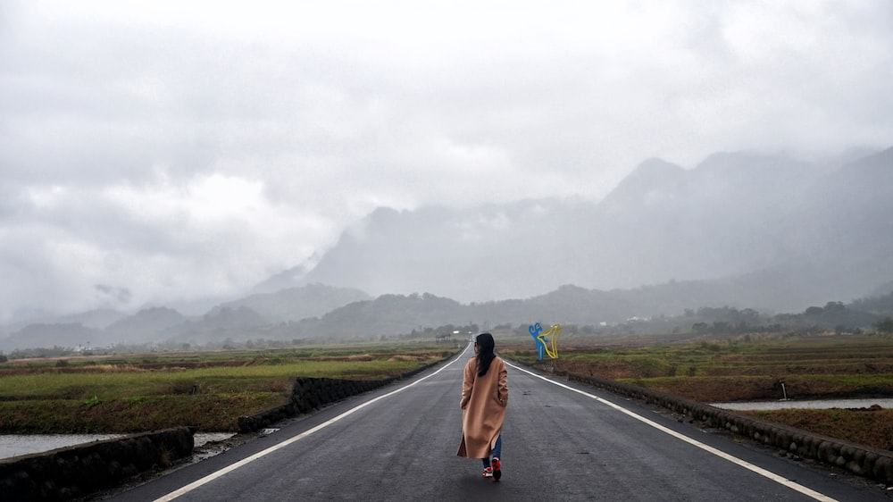 woman walks on gray concrete road during daytime