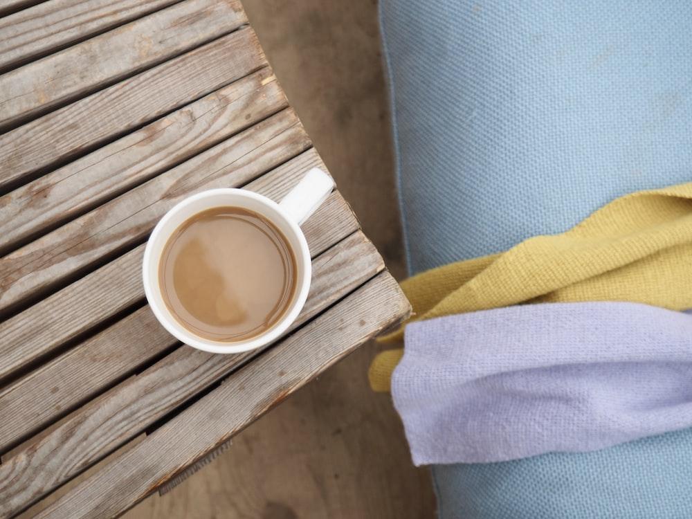 coffee filled ceramic mug on brown wooden panel