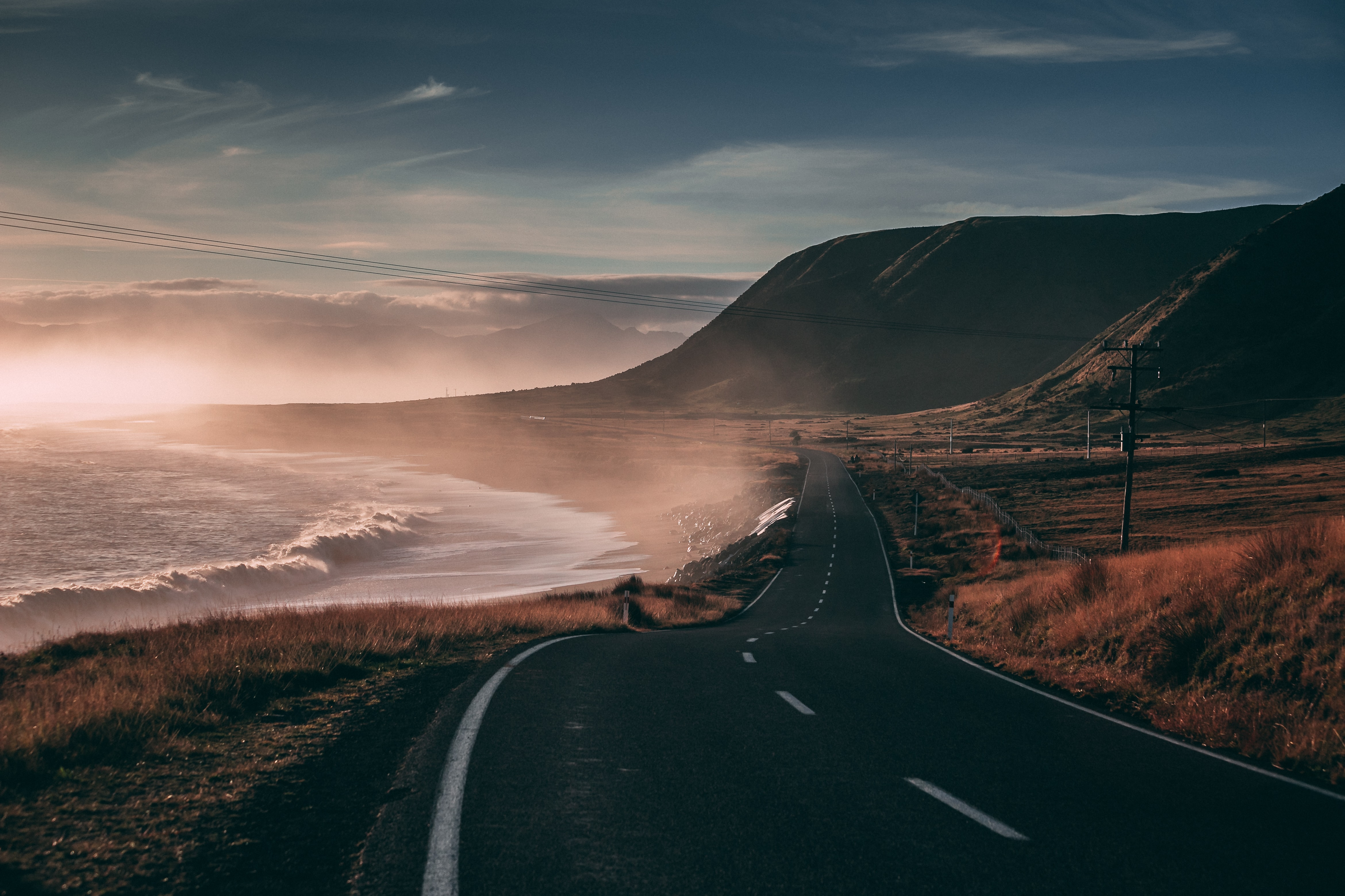 black road besides seashore and mountain at sunset