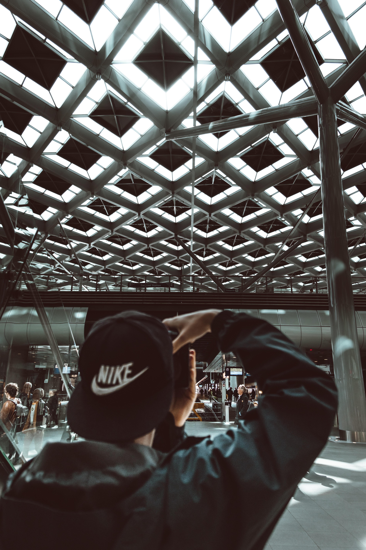 man wearing black Nike flat brimmed cap holding camera