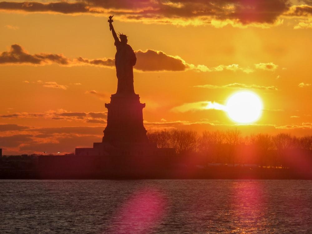 silhouette of Statue of Liberty under orange sunset
