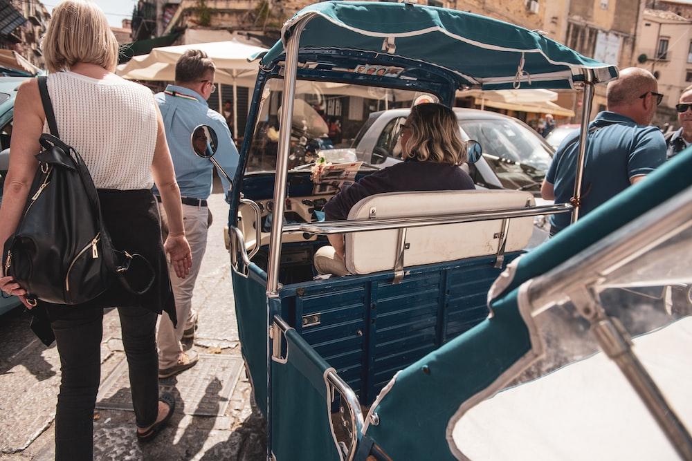 woman riding on auto rickshaw during daytime