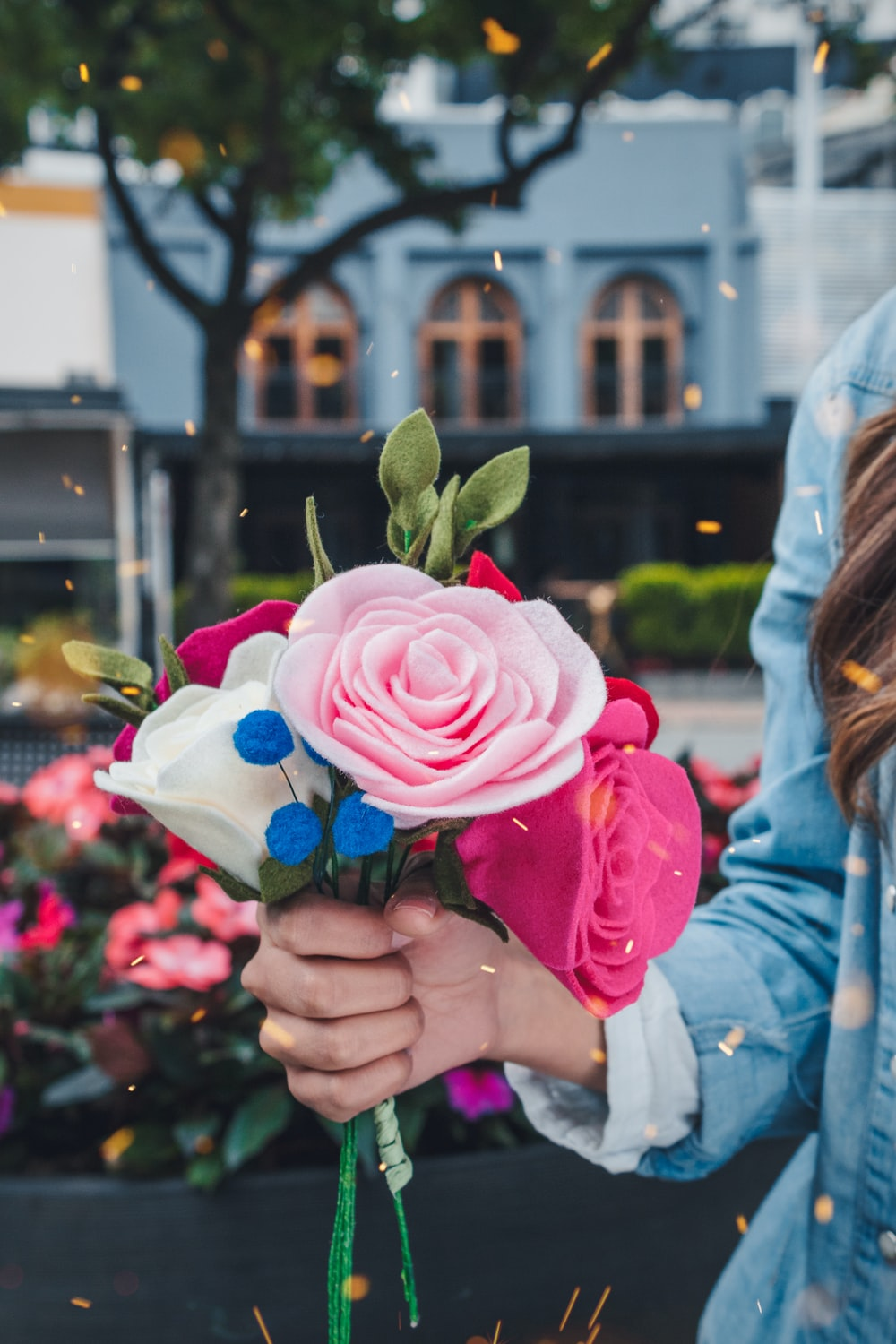 woman holding pink and white petaled faux flower