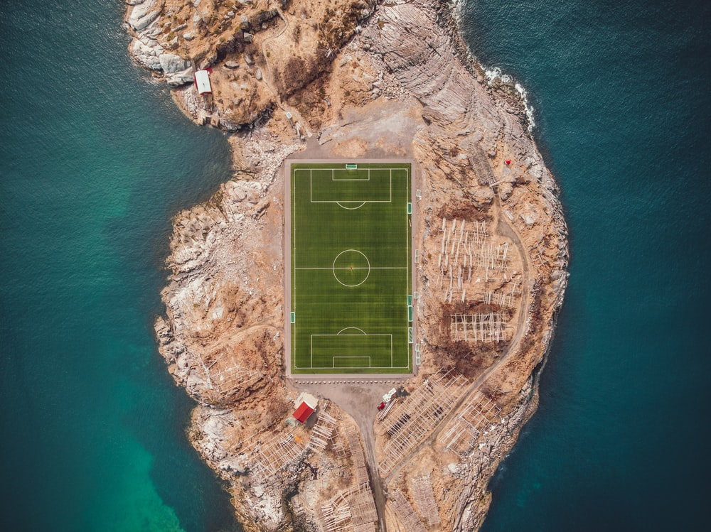 aerial photography of soccer field near body of water
