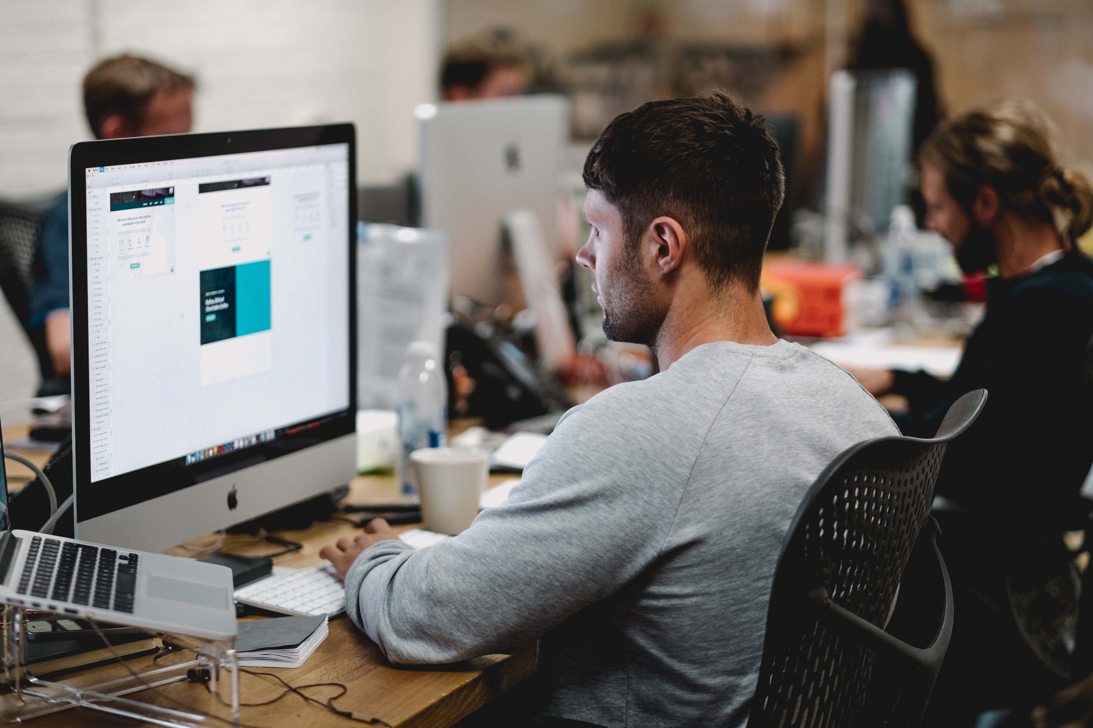 man in gray sweatshirt sitting on chair in front of iMac