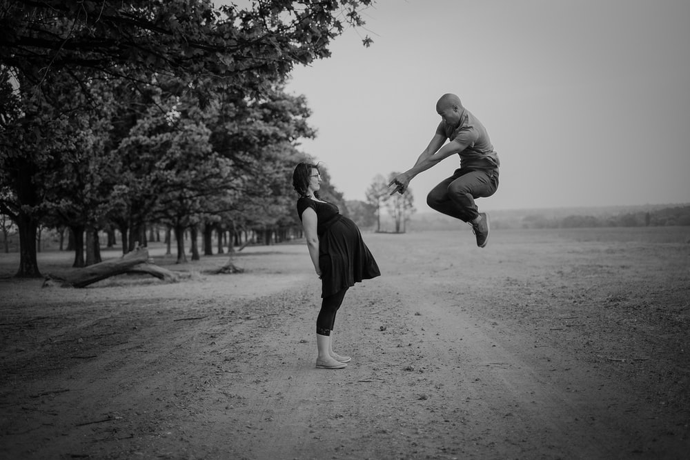 grayscale photo of man jumping in front of pregnant woman near trees during daytime