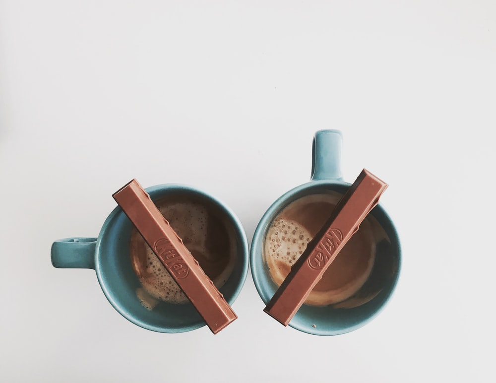 two green ceramic cups with chocolate bar on top