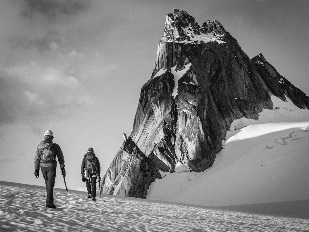 grayscale photo of two people walking on mountain valley