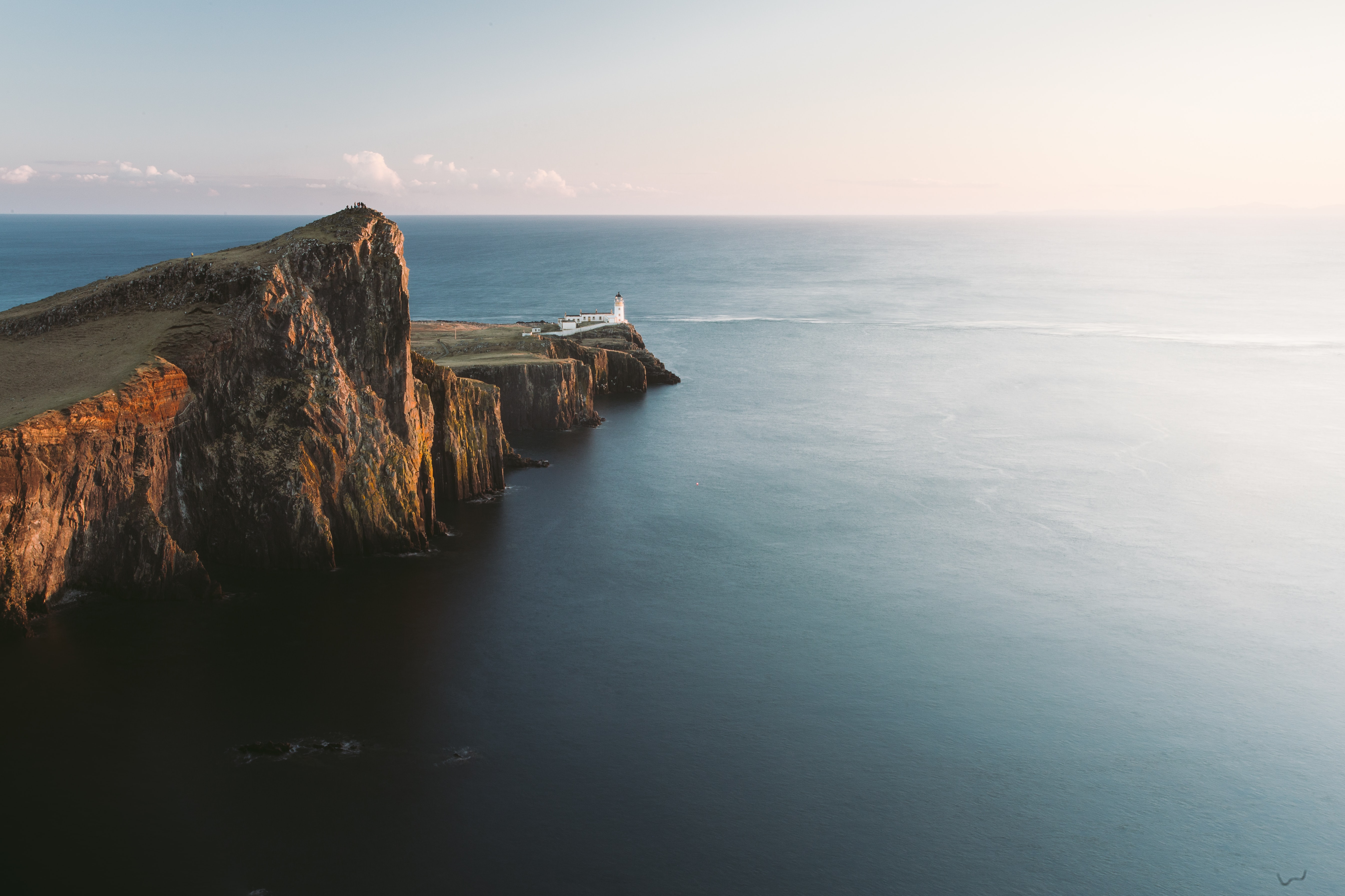 brown mountain cliff beside of blue ocean aerial photography