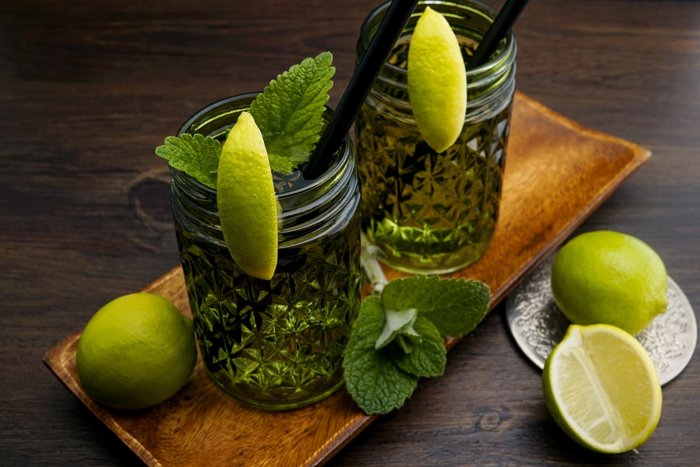 clear glass jar with green lemon and water