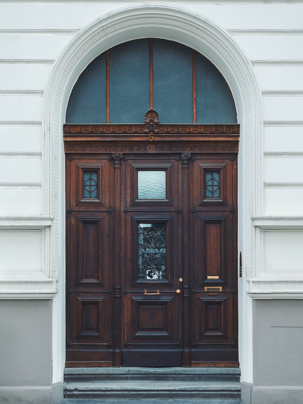 closed brown wooden door of white building