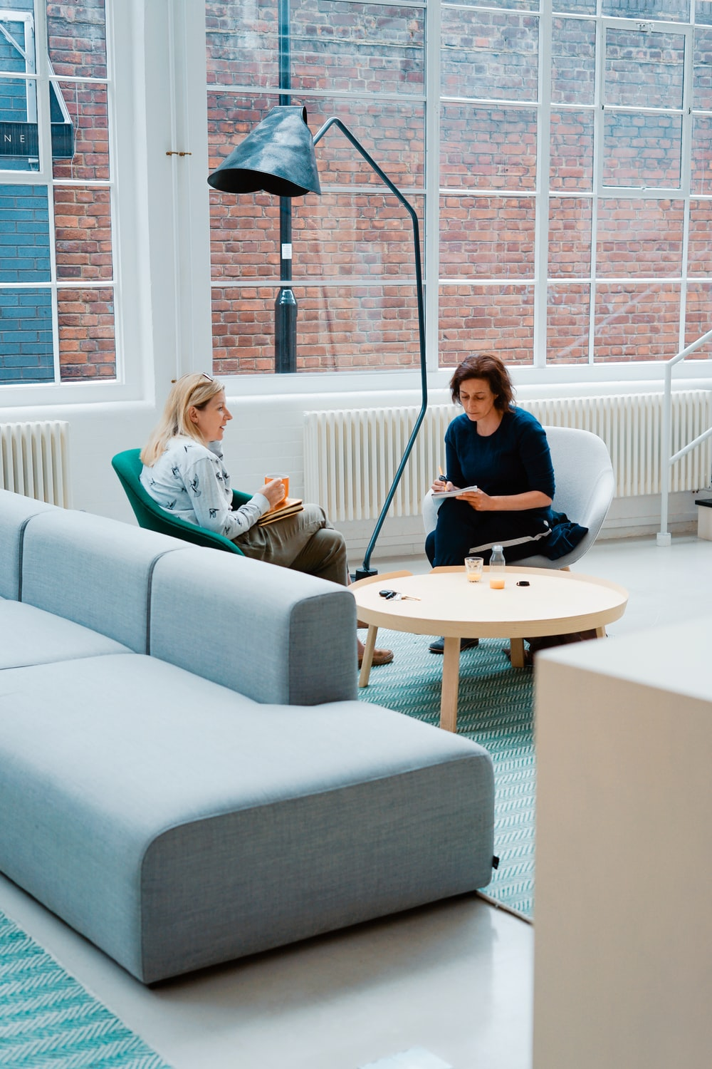 two woman sits on sofa chairs inside house