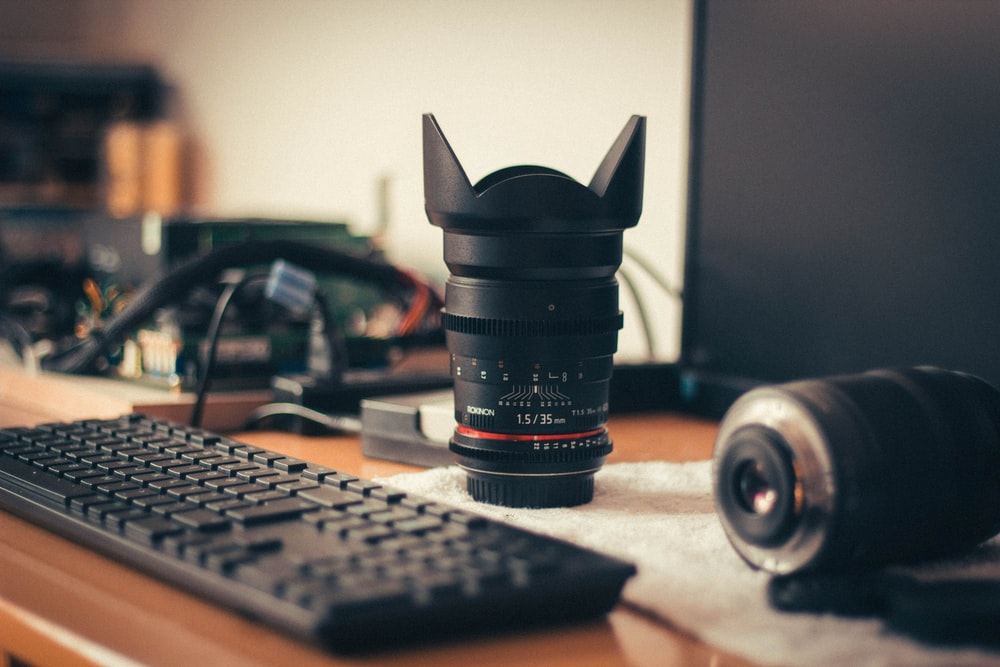 photo zoom lens near keyboard and monitor on tabletop