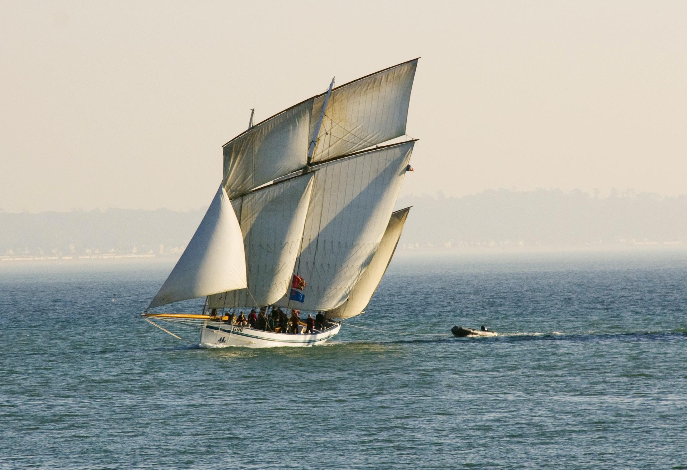 white sail boat sailing at the sea