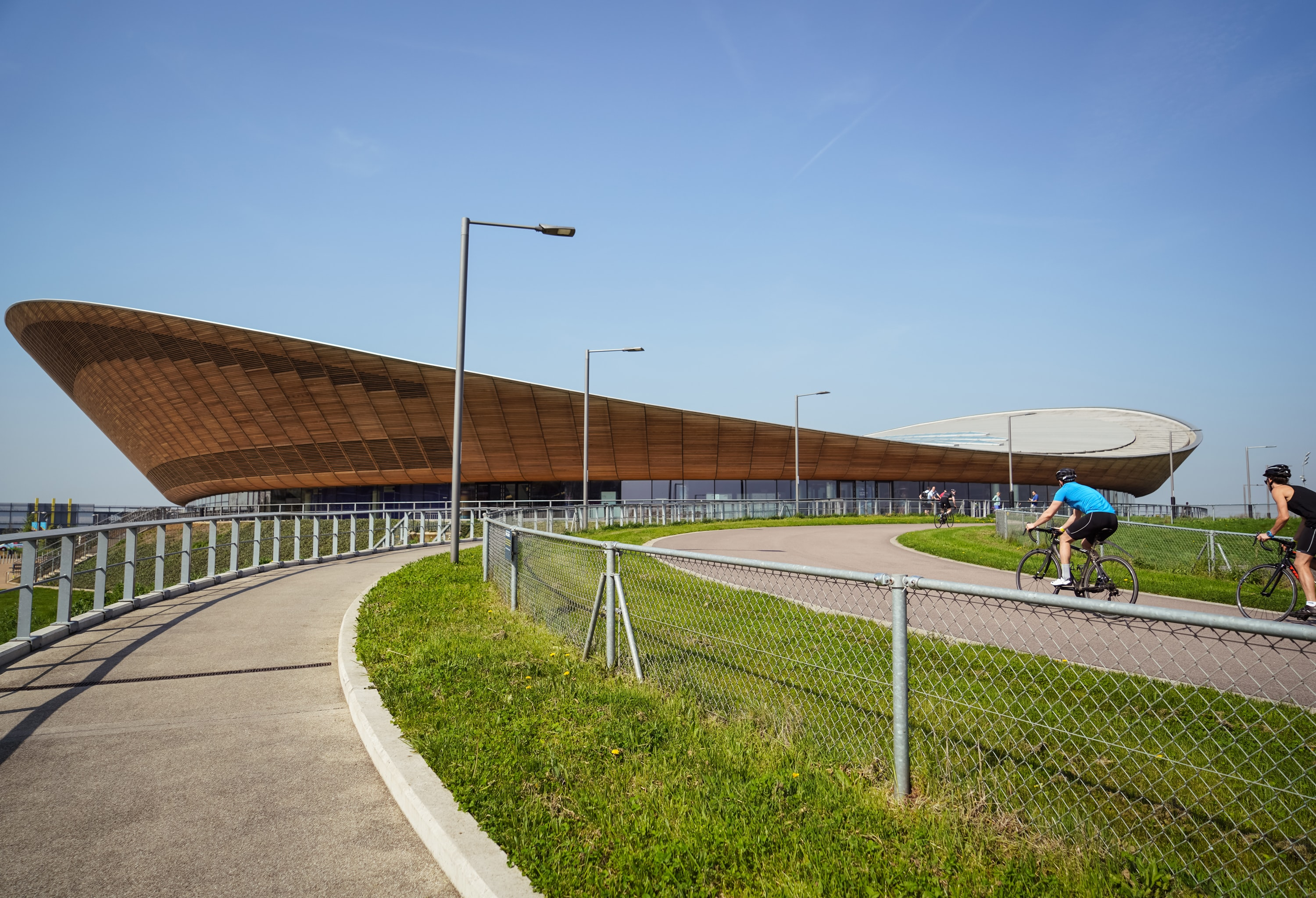 two cyclist on road near stadium at daytime
