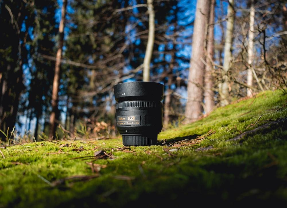 black DSLR lens on green grass shallow focus photography
