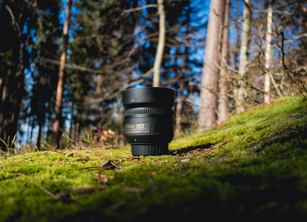 black DSLR lens on green grass shallow focus photography