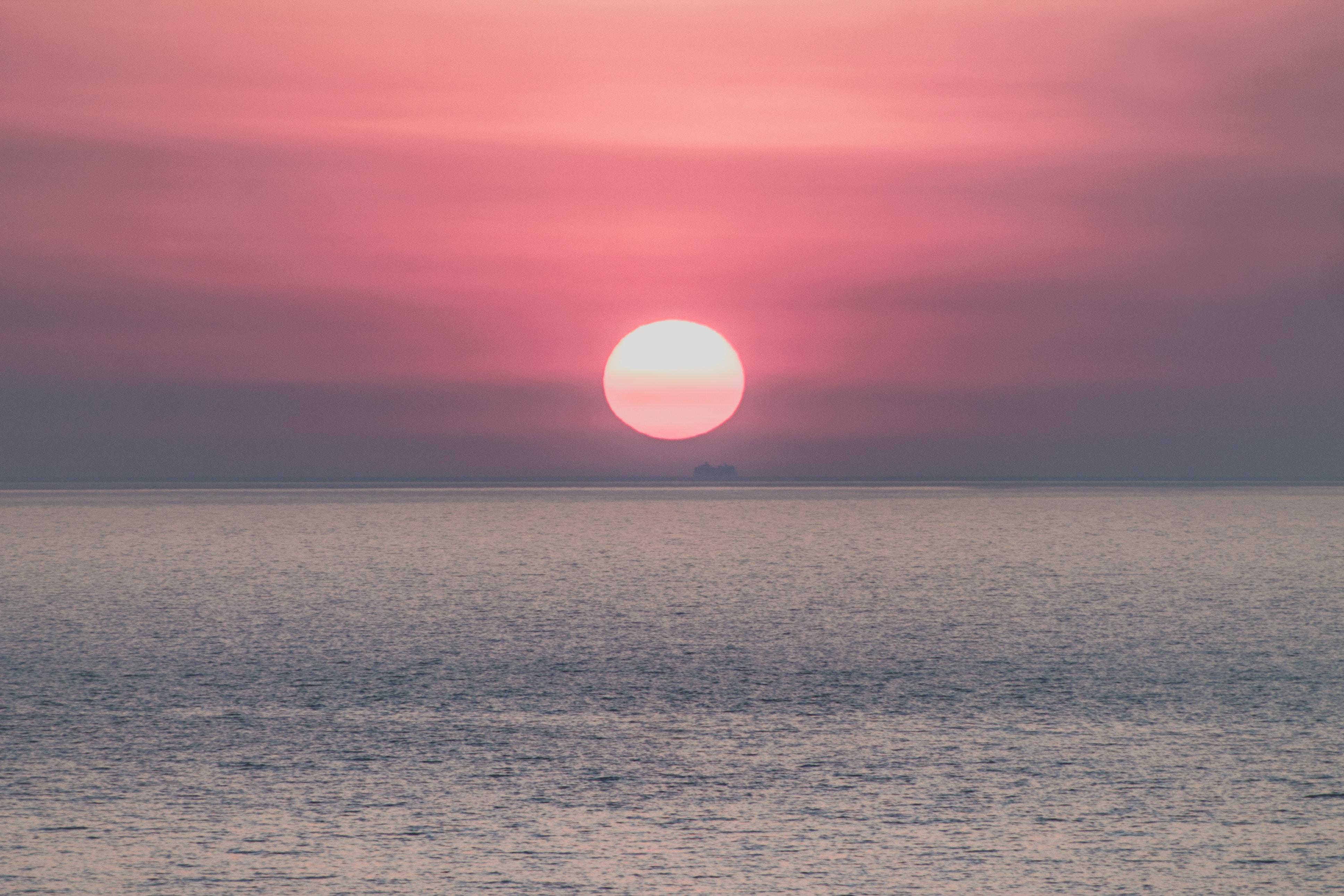 sun setting on ocean horizon