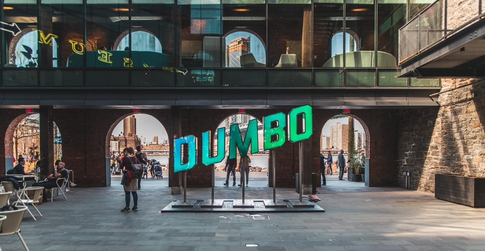 people walking near Dumbo signage