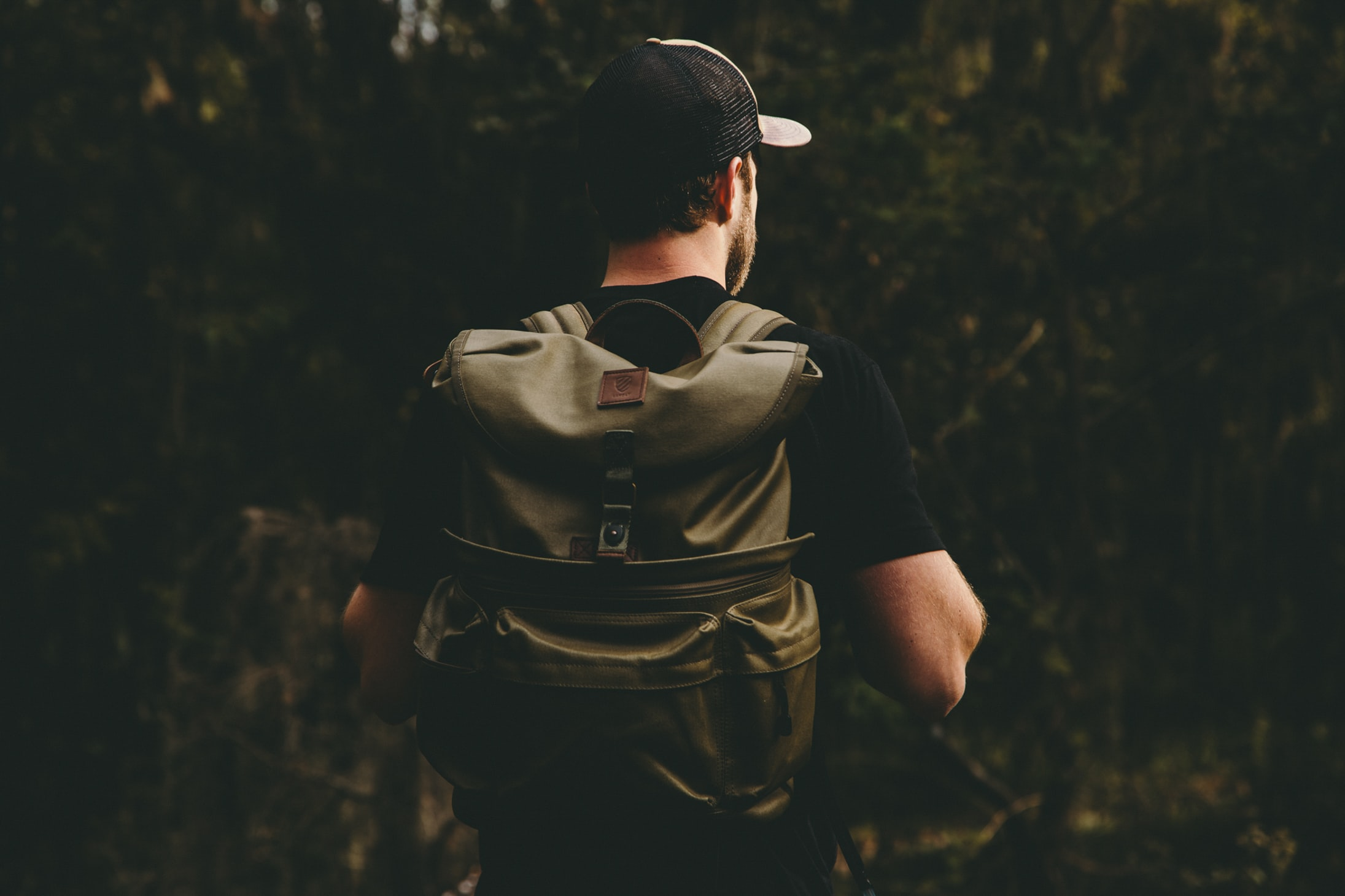 man at forest carrying brown backpack