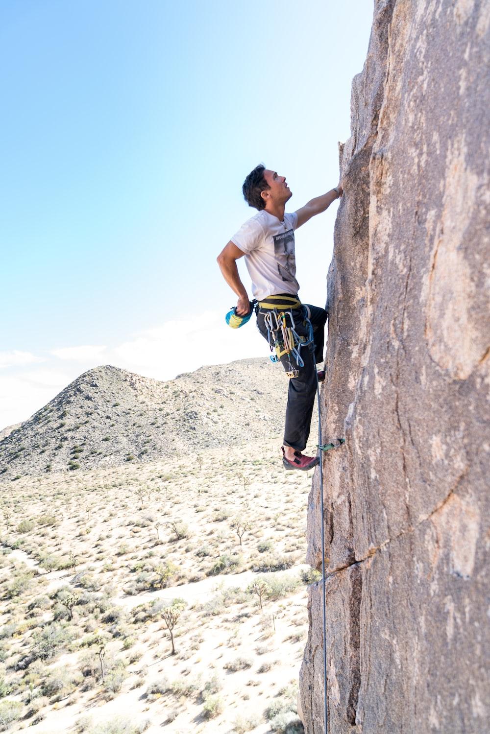 man climbing a mountain during daytime