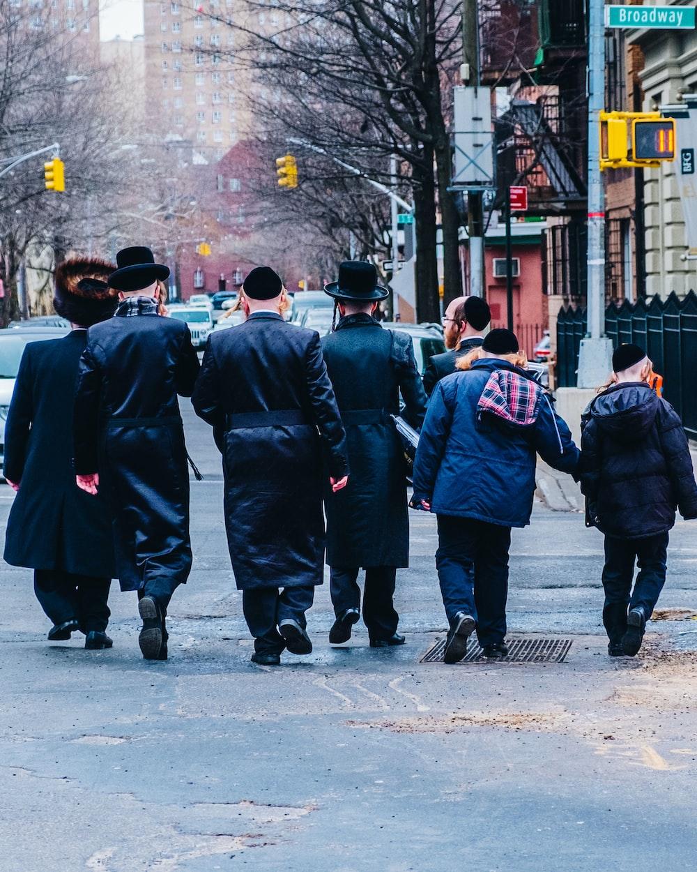 group of men in black coat walking on sidewalk during daytime