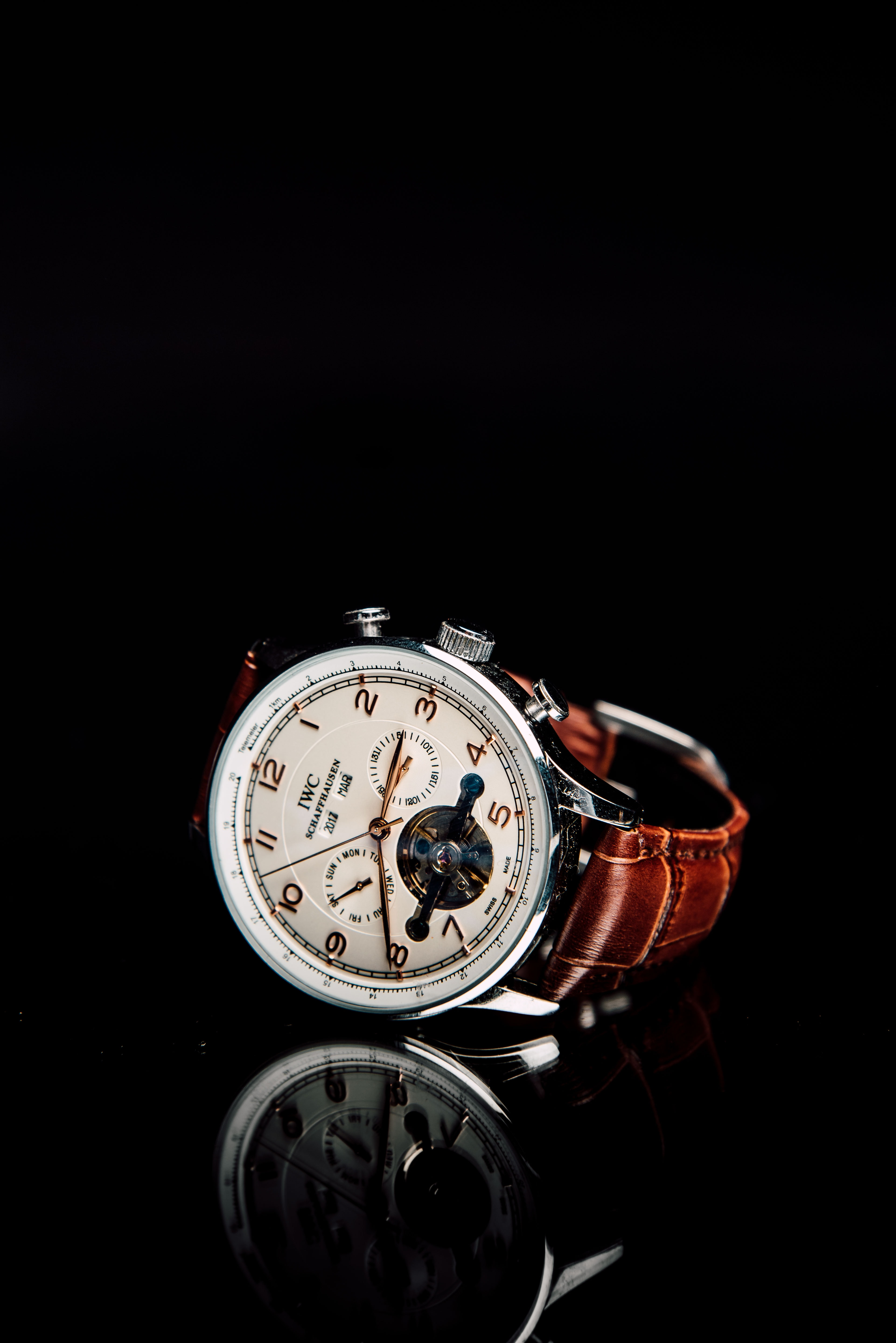 round silver-colored chronograph watch with brown leather strap